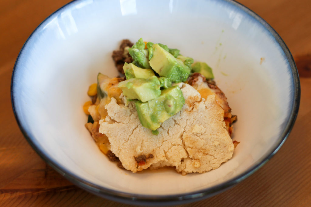 Bowl of Mexican beef cobbler topped with avocado