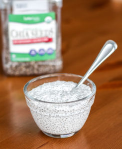 Bowl of vanilla chia seed pudding with container of chia seeds in background
