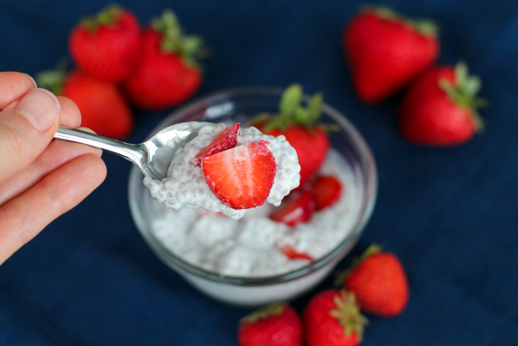 Hand holding up spoon filled with strawberry cheesecake chia seed pudding