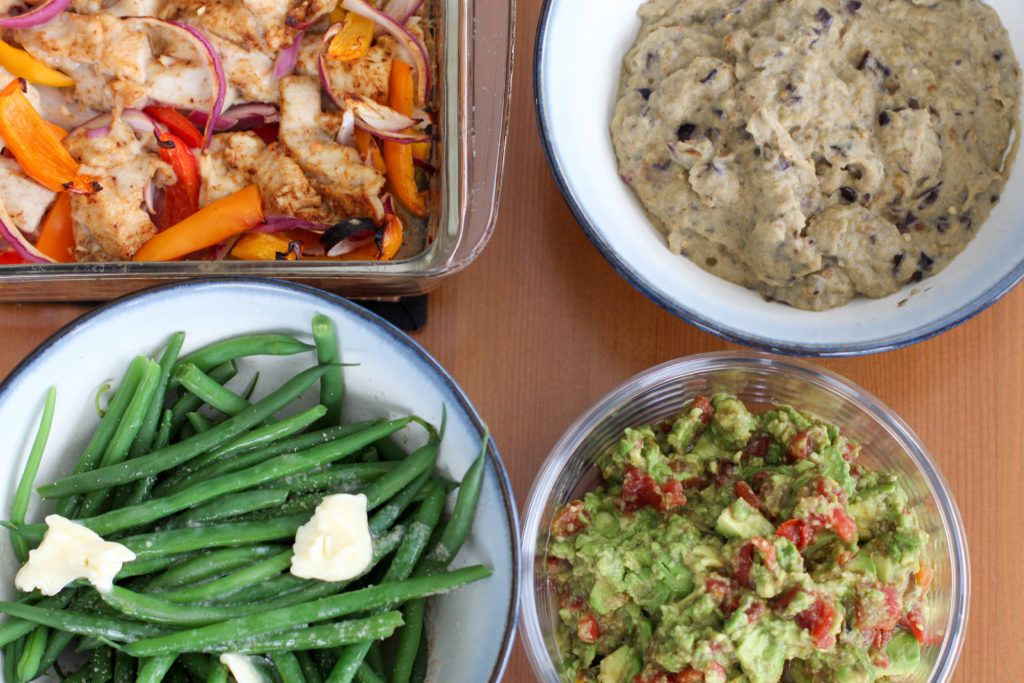 Table filled with chicken fajitas, bean-less refried beans, guacamole, and green beans