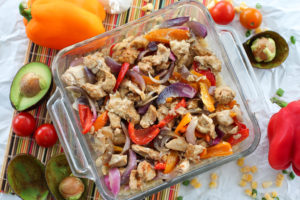 Glass dish of baked chicken fajitas surrounded with veggies