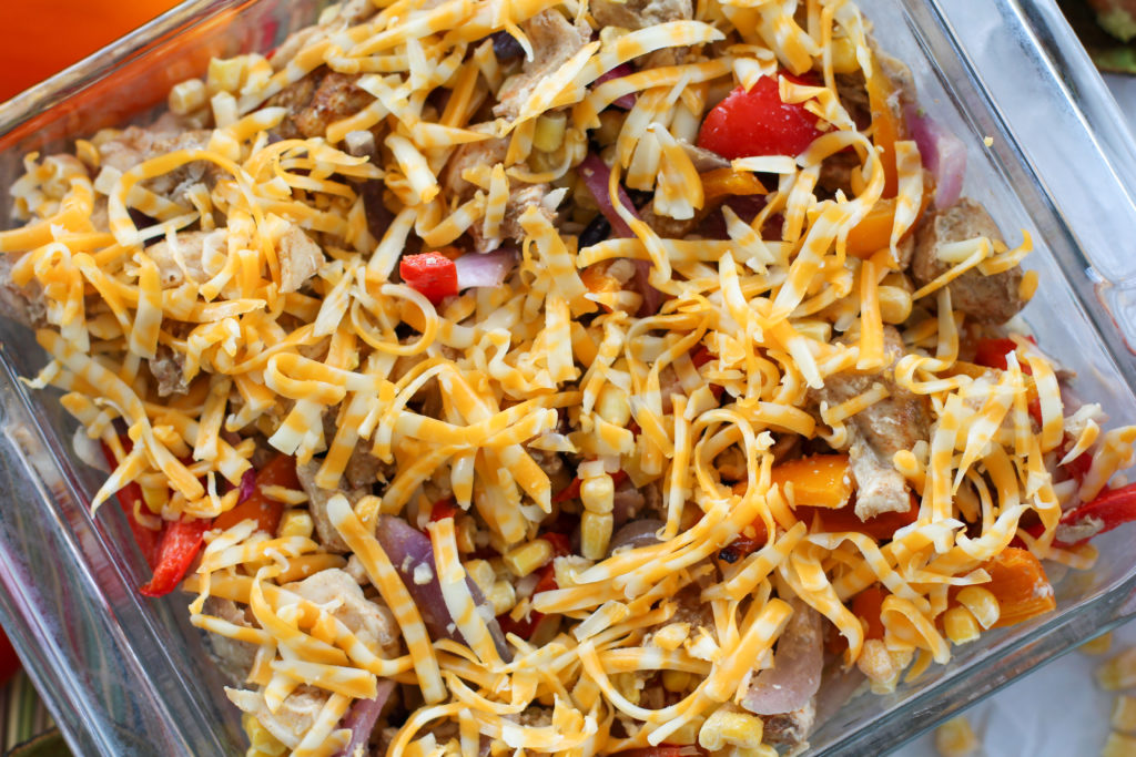 Pan of chicken fajita casserole topped with shredded cheese