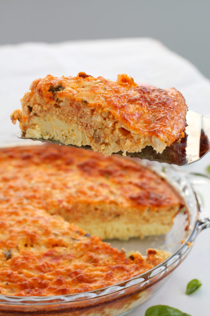 pie server holding a slice of tomato basil egg casserole