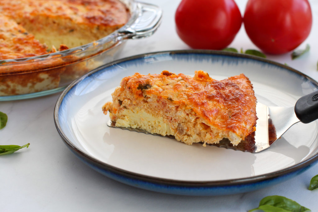 pie server holding slice of tomato basil egg casserole