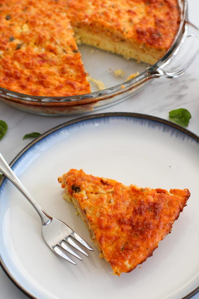 Slice of tomato basil egg casserole on plate
