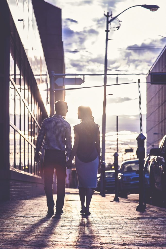Couple walking and holding hands on sidewalk - physical touch - 5 love languages check-in