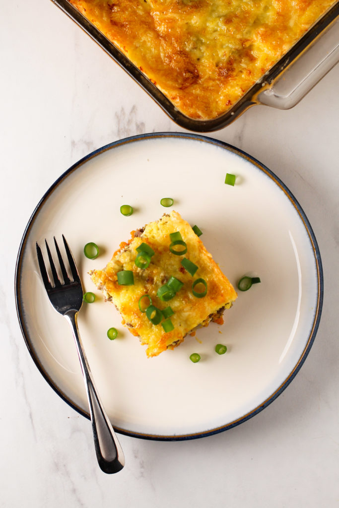 fork next to white plate with egg casserole topped with green onion
