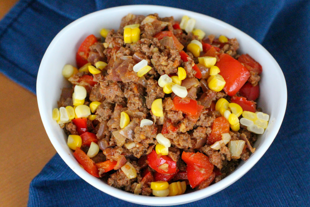 Homemade taco meat with corn and red bell pepper in white bowl