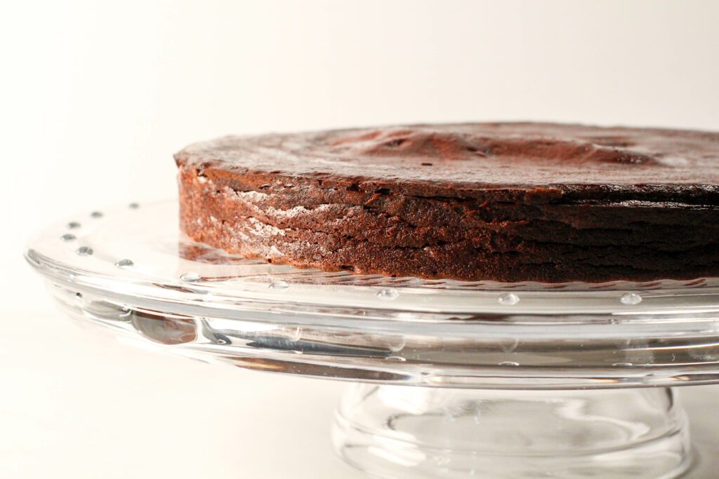 side view of torte without ganache sitting on glass cake plate
