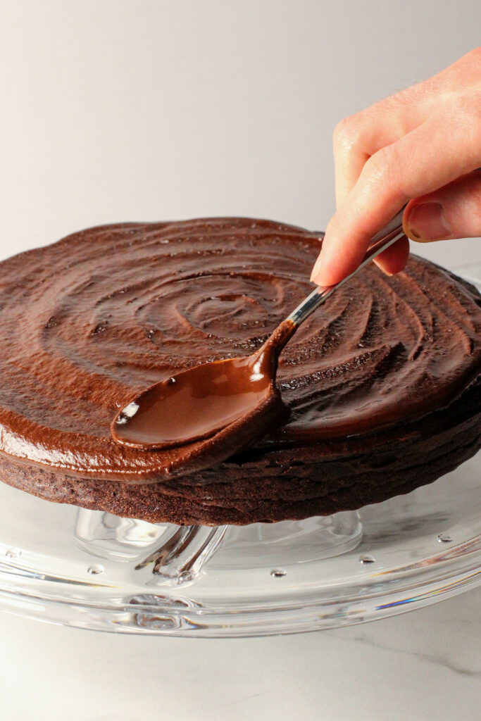 hand using spoon to spread chocolate ganache on top of red velvet torte