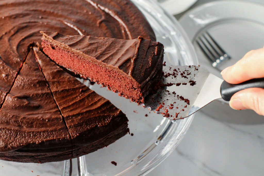 hand holding spatula with piece of red velvet torte