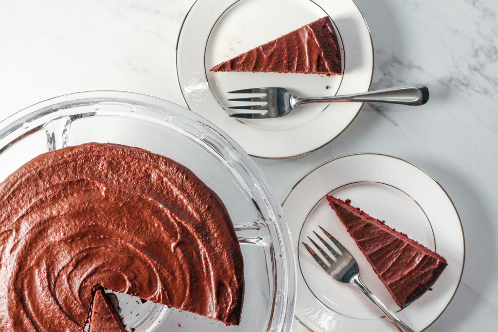 overhead view of torte and two plates with slices of red velvet torte