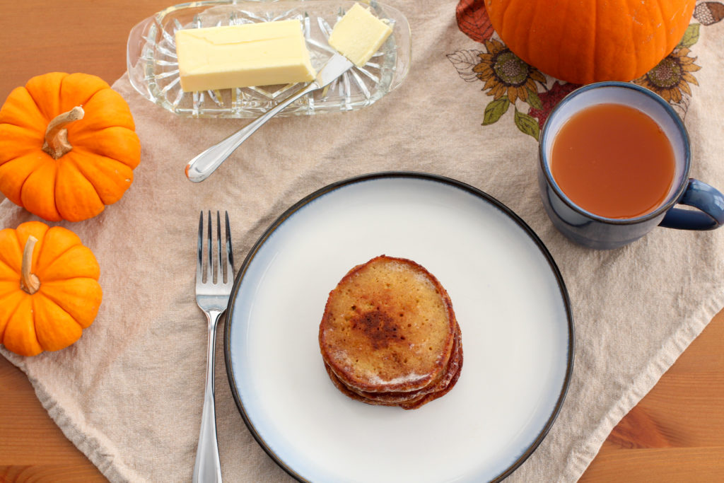 Table setting with pumpkin, butter, pancakes, and cider
