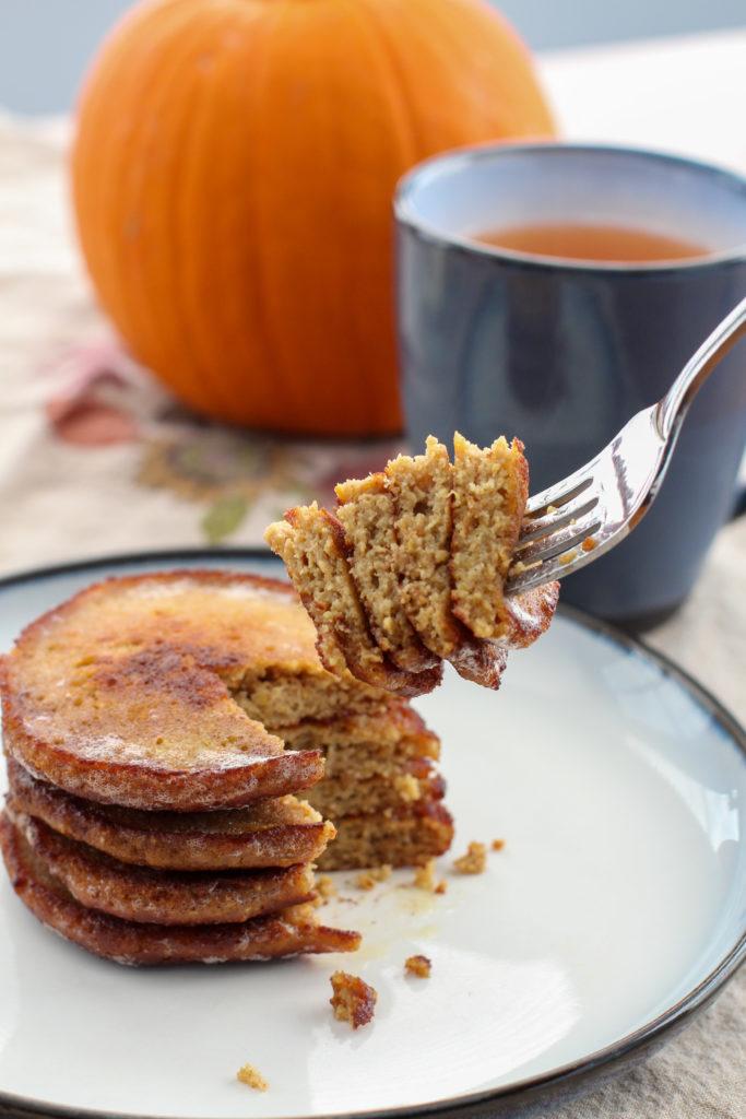 Fork holding bite of pumpkin pancakes