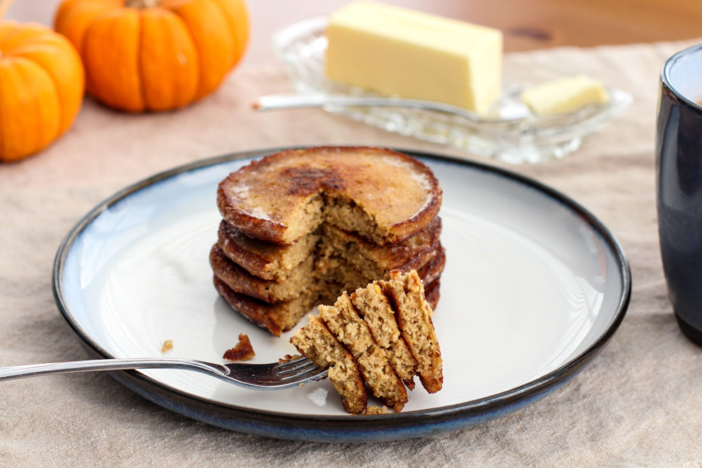 Pumpkin pancakes stacked on plate with a forkful ready to be eaten