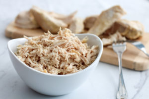 bowl of shredded chicken with cutting board of cooked chicken