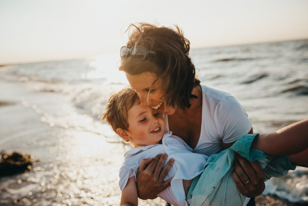 Mom holding son at the beach
