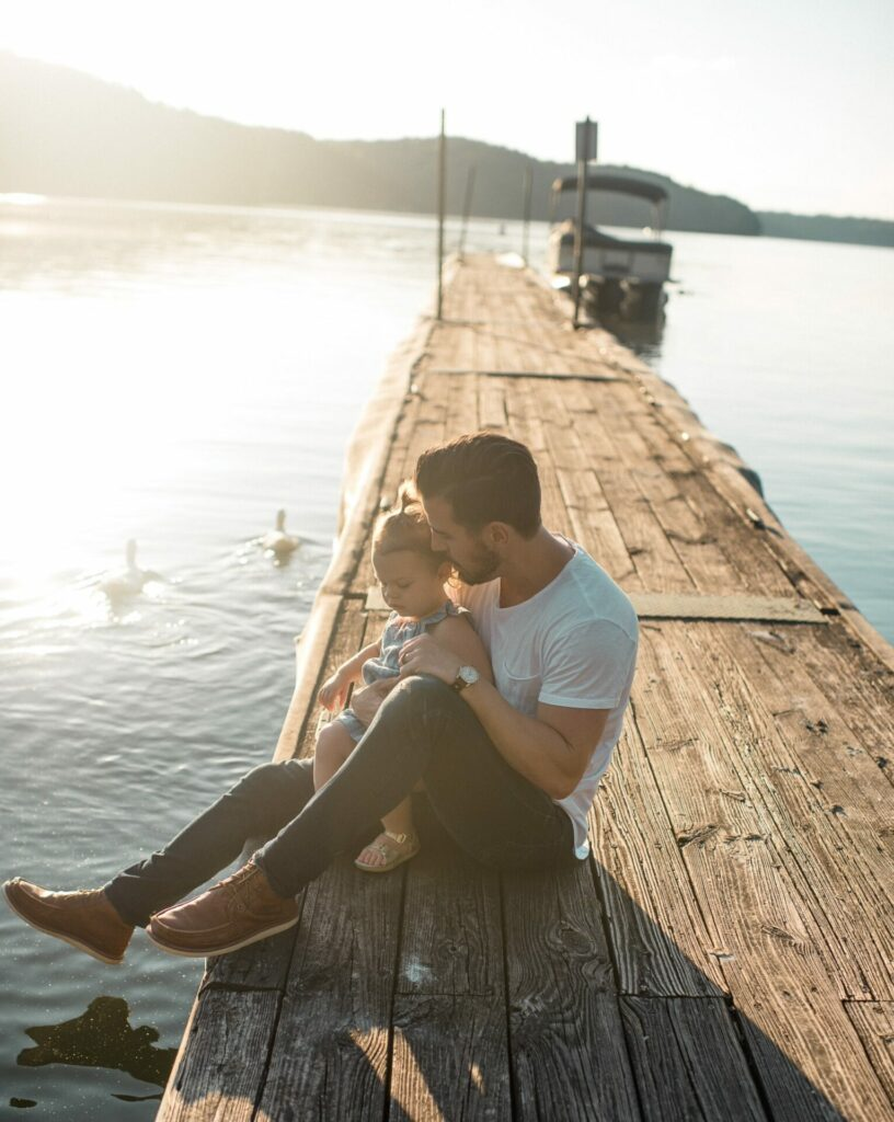 child sitting on pier with dad