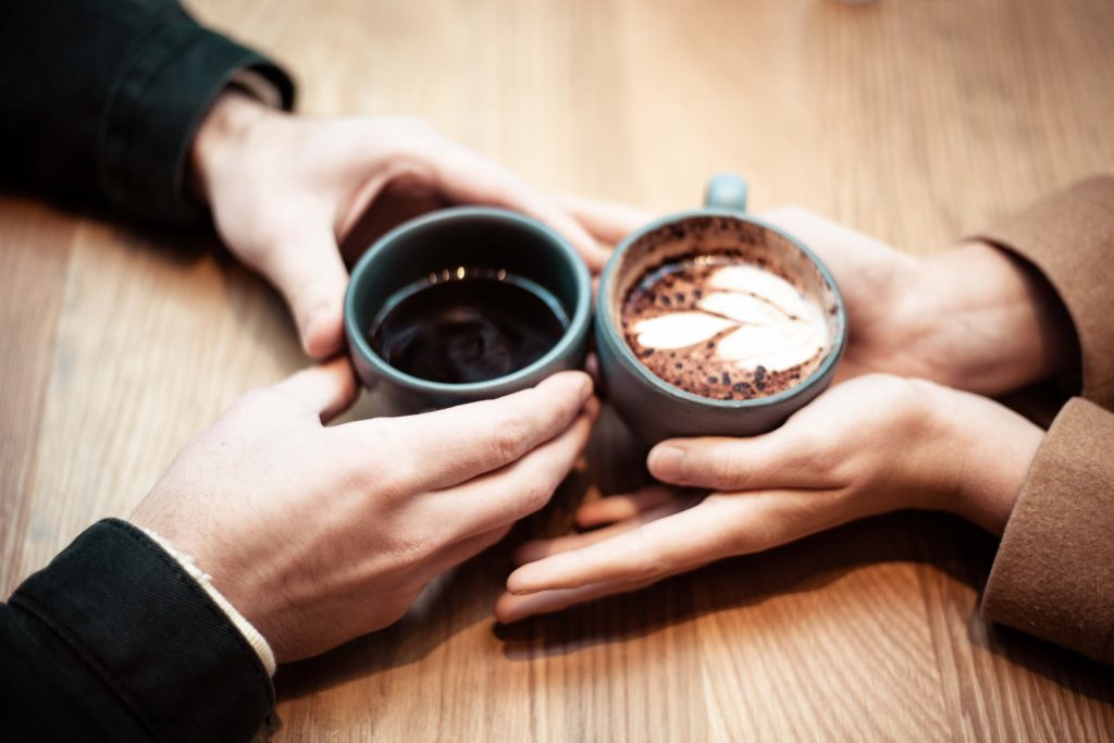 close up couple holding coffee mugs