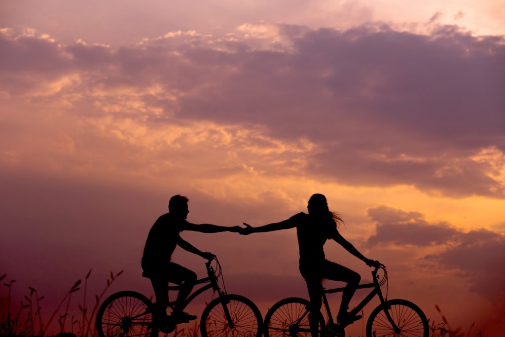 couple on bikes at sunset