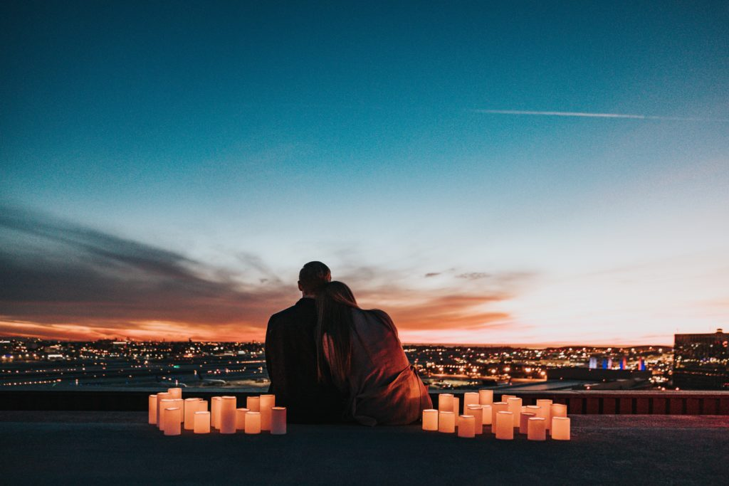 couple sitting with candles surrounding them watching sunset