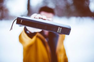 man in yellow coat holding bible out in front