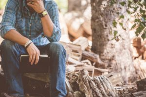 man sitting near wood pile holding bible