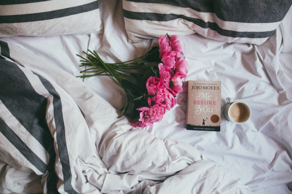 flowers, book and coffee lying on bed - 5 love languages gifts