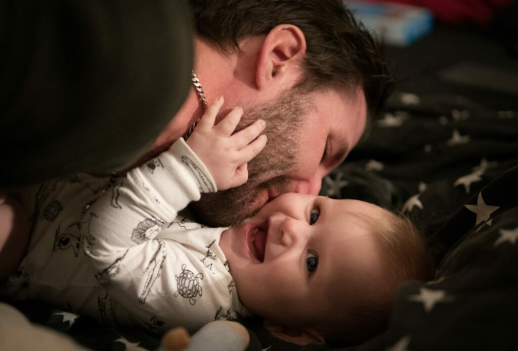dad kissing little girl who is smiling