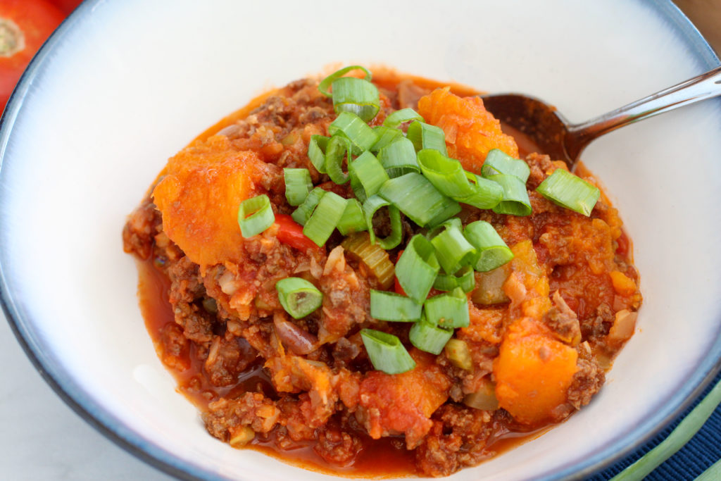 Bowl of butternut squash chili topped with green onion