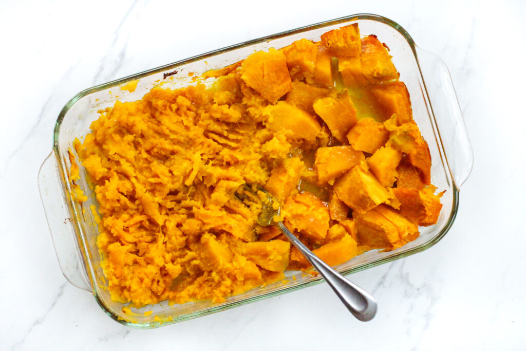 baking dish full of buttercup squash with half smashed by a fork laying in pan