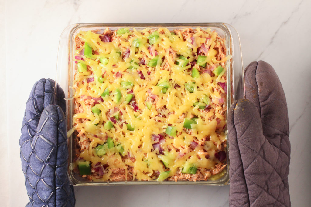 two oven mitts holding BBQ Chicken Casserole