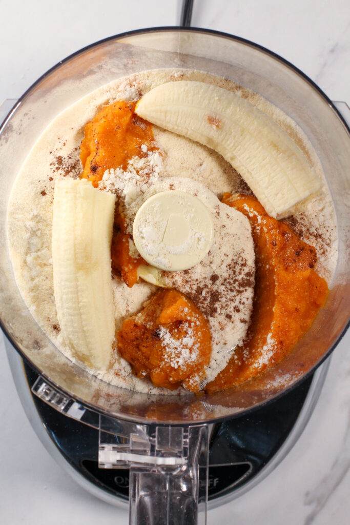 food processor filled with pumpkin pie truffle ingredients