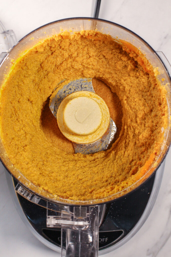 food processor filled with blended pumpkin pie truffle ingredients