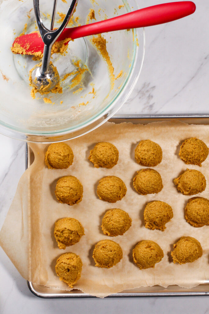 empty bowl with scatula and full cookie tray of pumpkin pie truffles