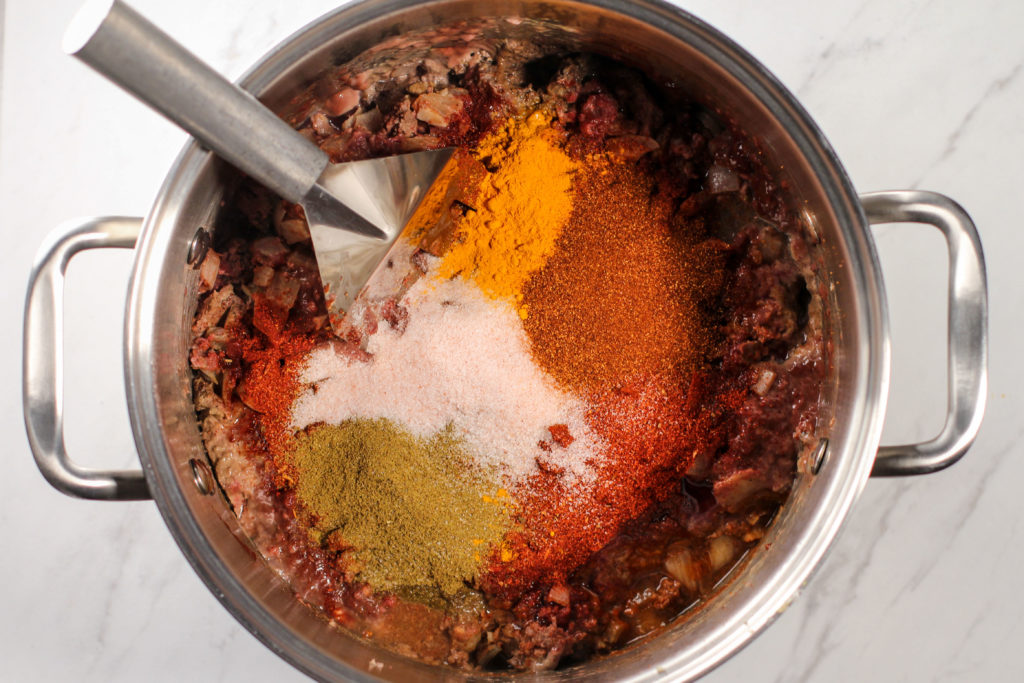 spices piled on top of cooking meat
