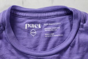 Pact 100% cotton on purple tshirt label