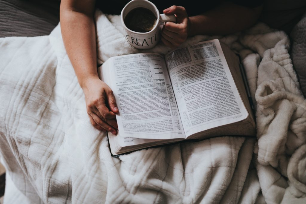 person holding coffee reading bible