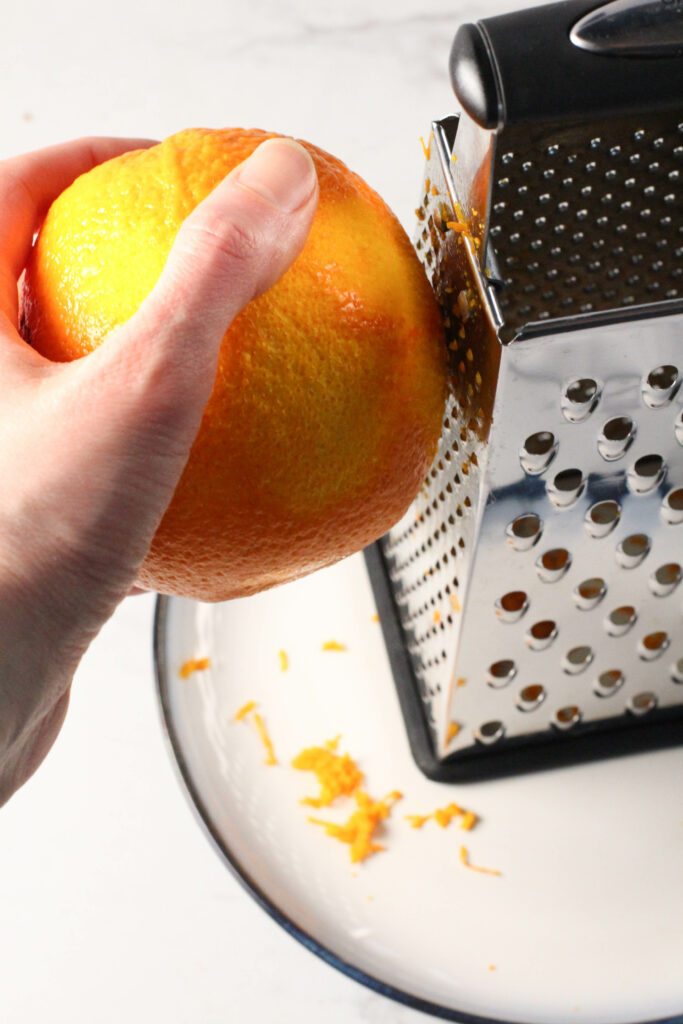 hand holding orange to zest it with a grater