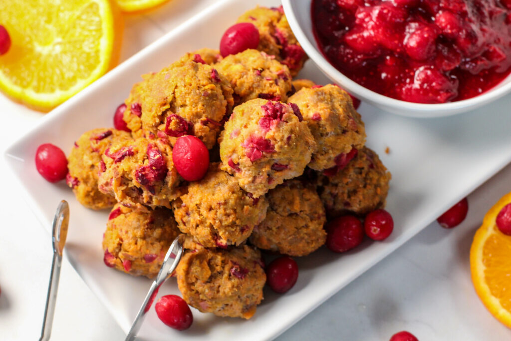 pile of cranberry orange meatballs next to dipping sauce