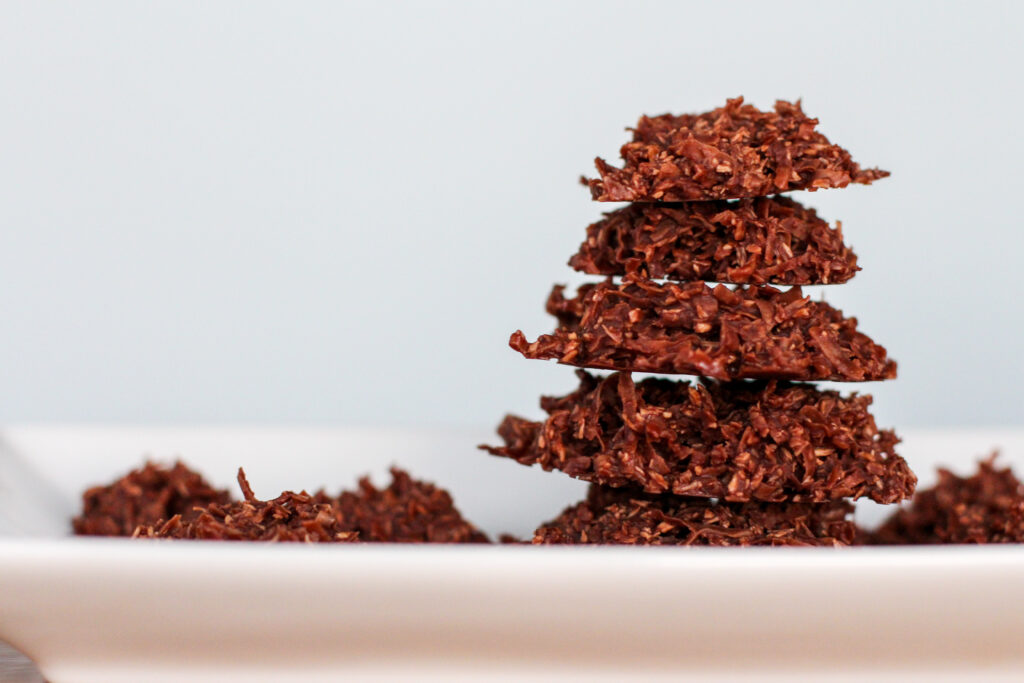 side view of no bake cookies stacked on white plate