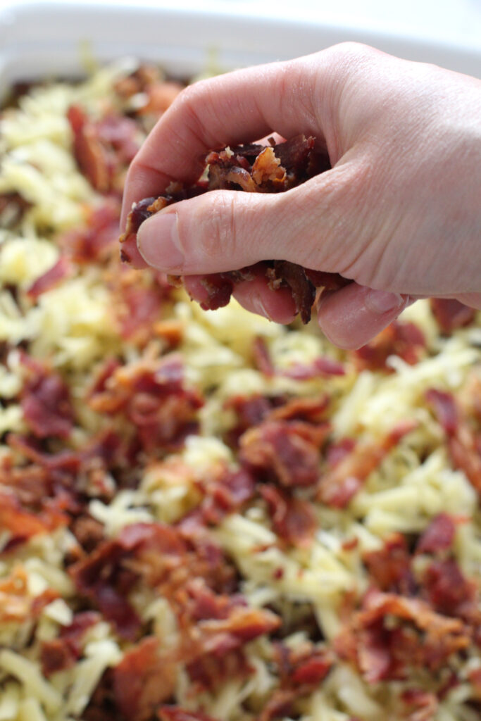hand holding bacon bits over casserole