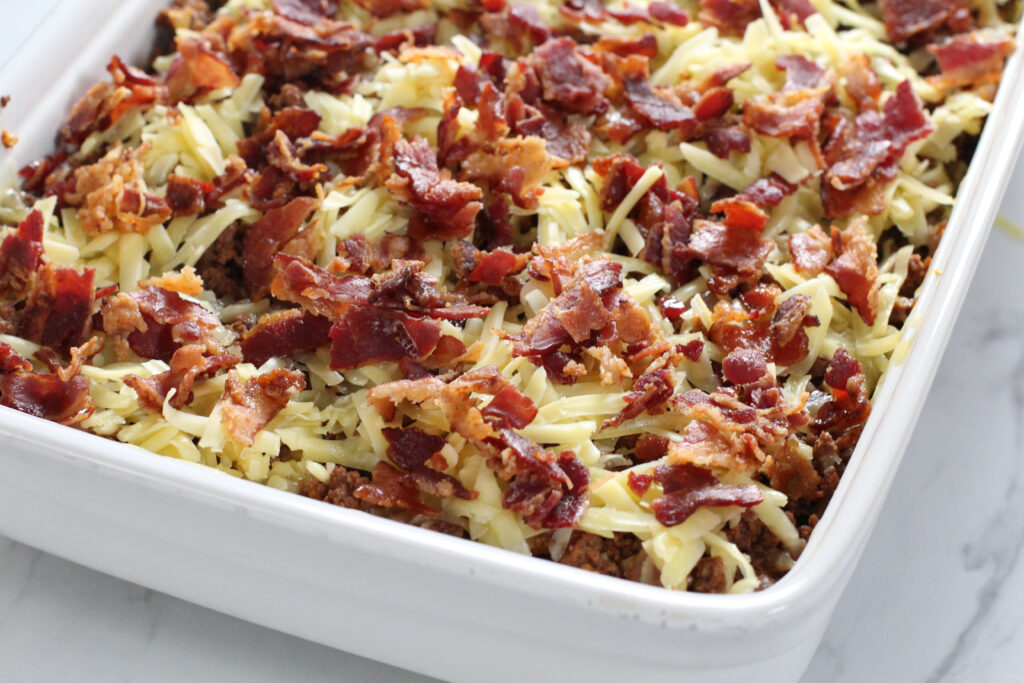 close up of melty cheese and bacon on casserole
