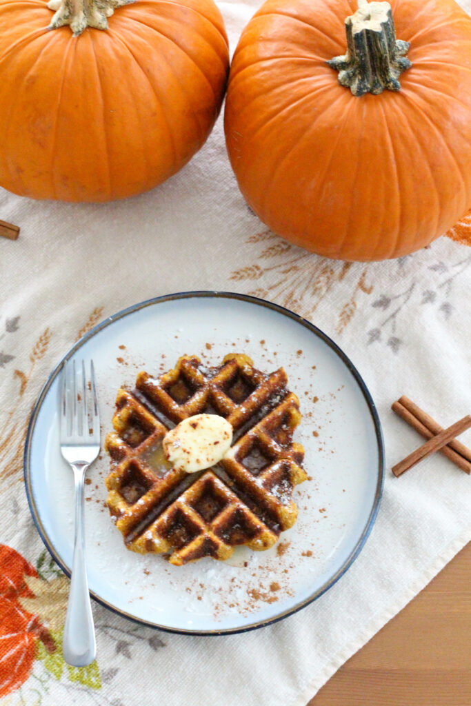 pumpkin waffle on plate with fork with pumpkins in background