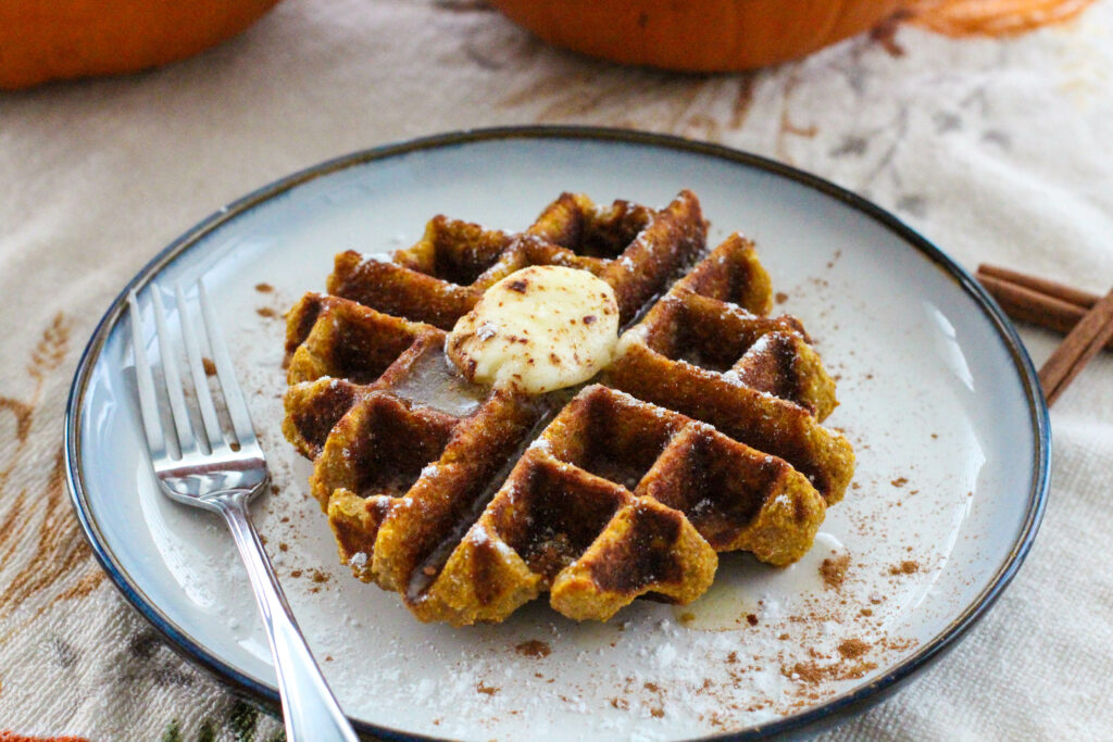 plate with pumpkin waffle topped with butter