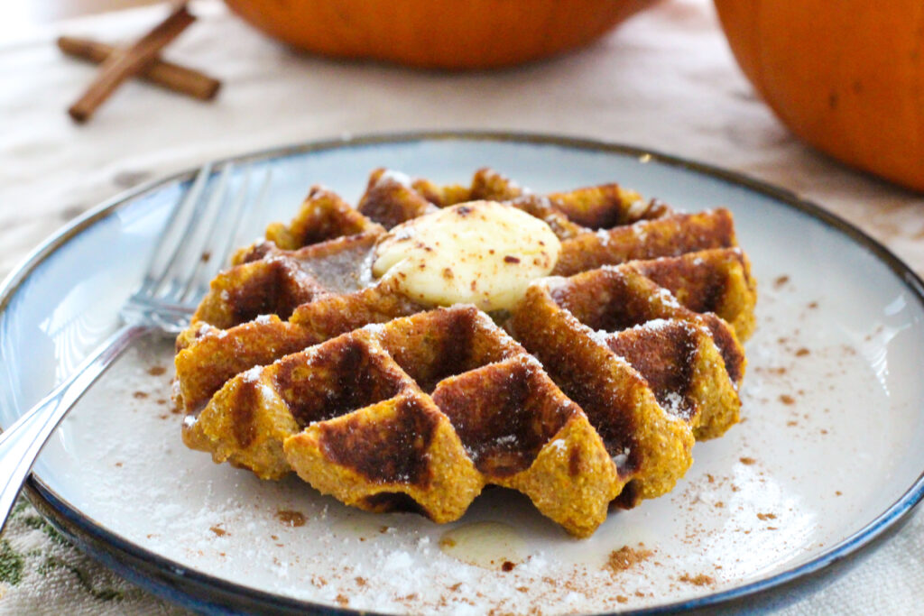 pumpkin waffle with pat of butter on topon plate with fork