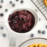 small white bowl with easy berry compote and spoon