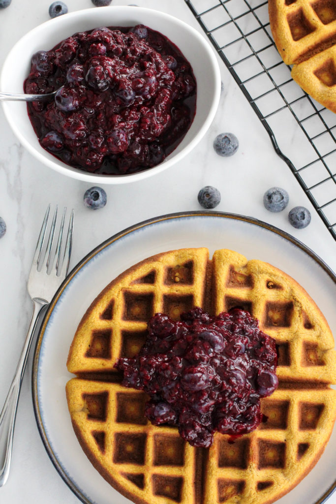 waffle and small white bowl of easy berry compote