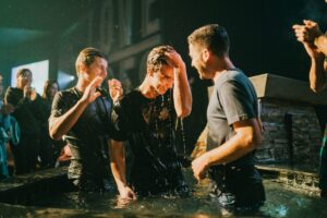 men baptizing another man with crowd clapping