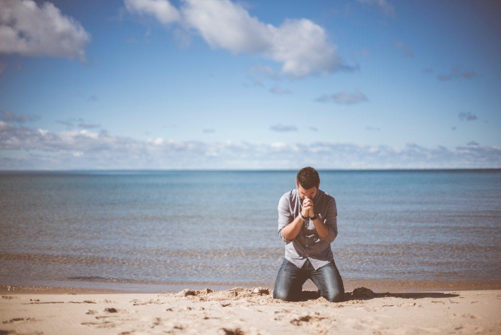 man kneeling in sand praying